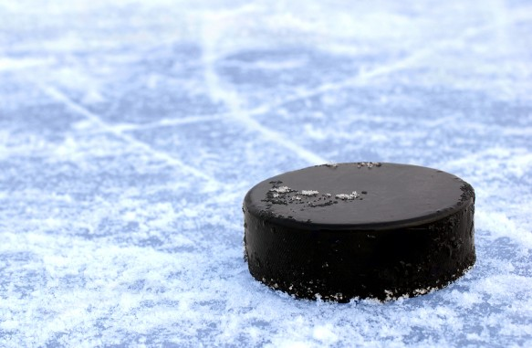 bigstock-black-hockey-puck-on-ice-rink-22755464