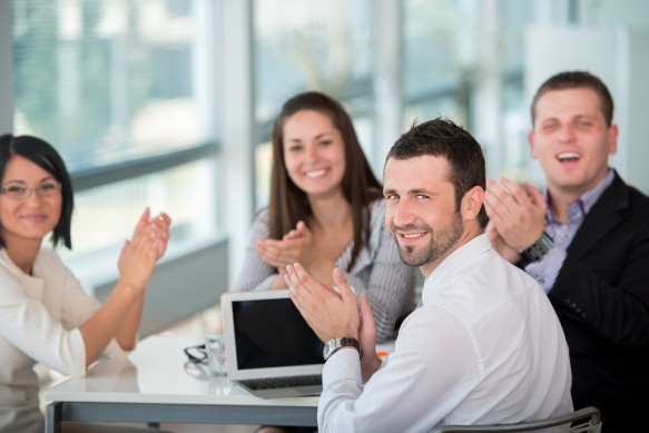 Happy team of business people posing in modern office environmen