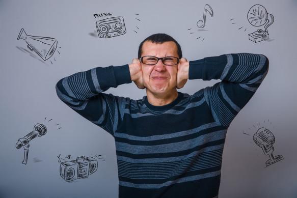 European man of thirty years in glasses closes her ears loud mus